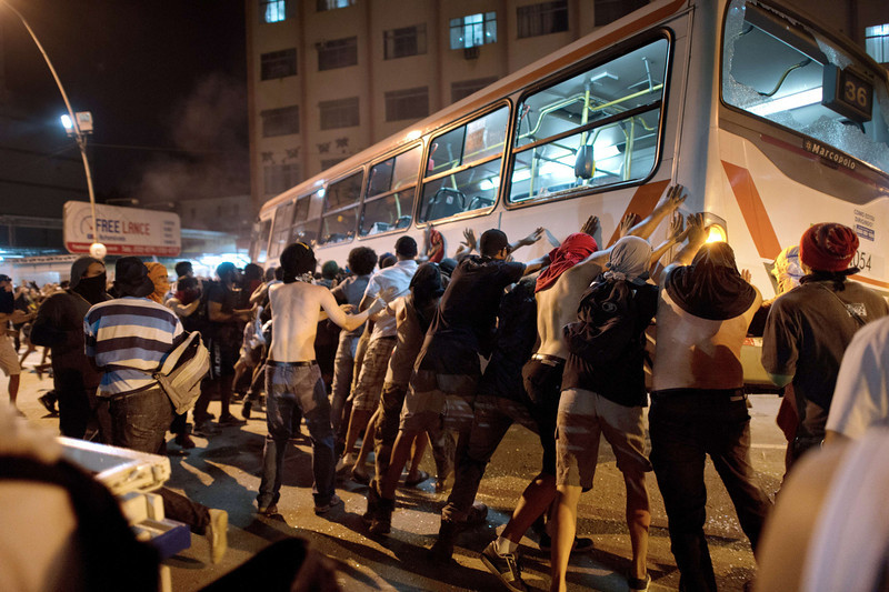 . Demonstrators try to overturn a bus late on June 19, 2013 in the center of Niteroi, 10 kms from Rio de Janeiro. Protesters battled police late on June 19, even after Brazil\'s two biggest cities rolled back the transit fare hikes that triggered two weeks of nationwide protests.  The fare rollback in Sao Paulo and Rio de Janeiro marked a major victory for the protests, which are the biggest Brazil has seen in two decades.   CHRISTOPHE SIMON/AFP/Getty Images