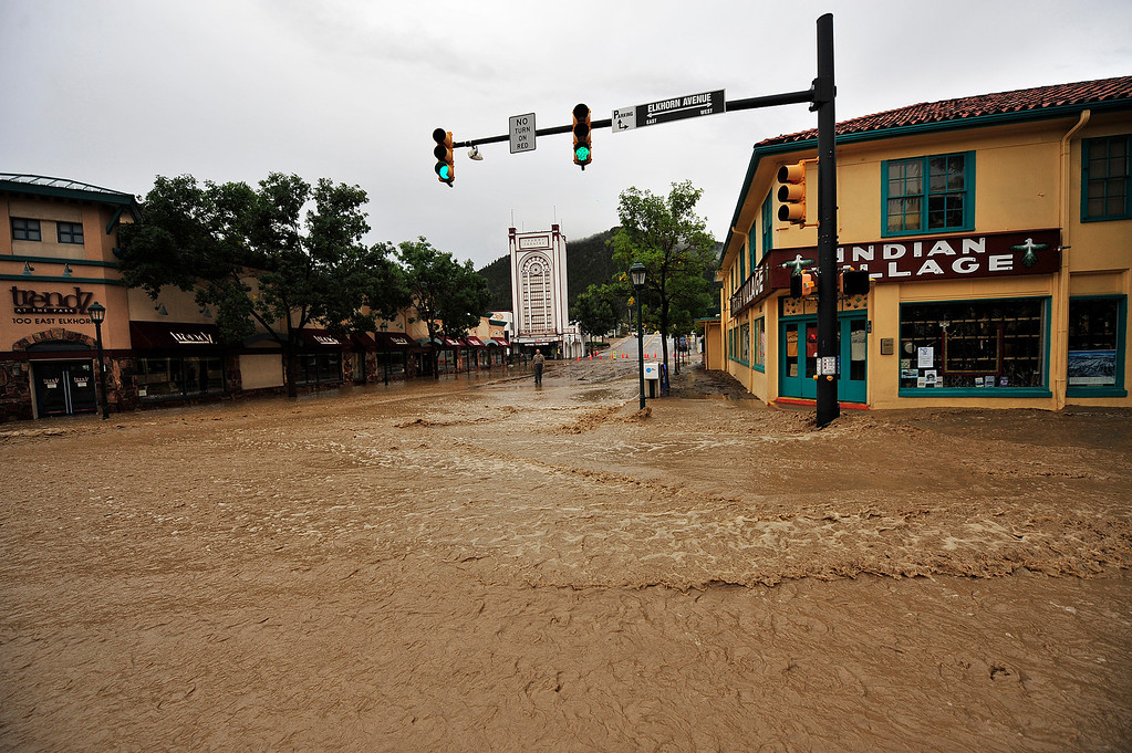 . Brown floodwater rushes through the intersection of Elkhorn and Morain avenues on Friday, Sept. 13, 2013. Town officials pointed out that the floodwater is untreated and not a safe place in which to splash around. Walt Hester/Estes Park Trail-Gazette