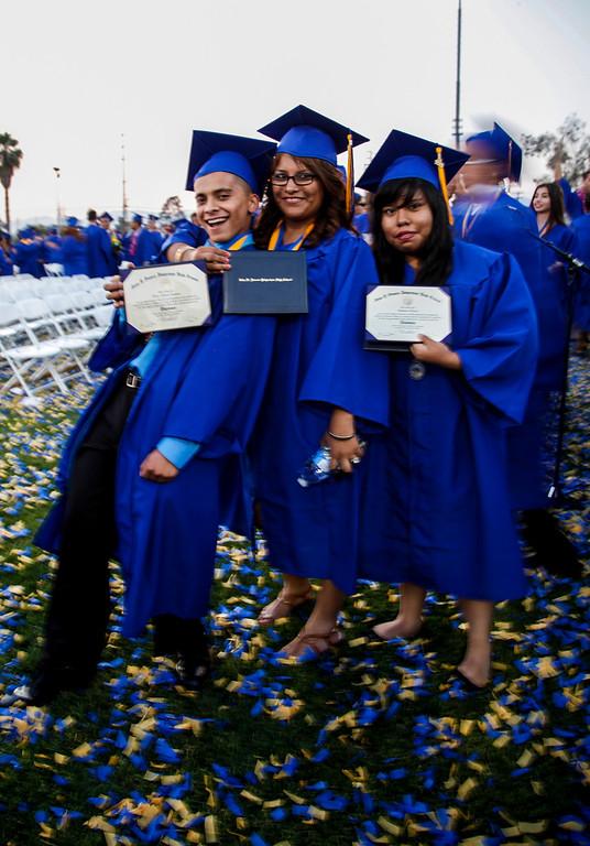 . Victor Carmona, Stephanie Linares and Maria Lino are new graduates surrounded by confetti, at John H Francis Polytechnic High School, Sun Valley, Calif., June 7, 2013. Photo: Lynn Levitt.