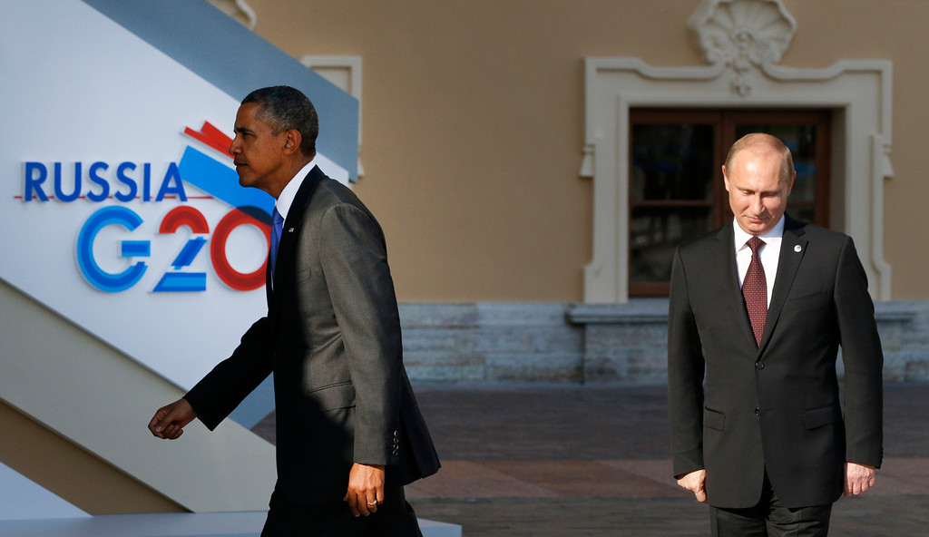 . U.S. President Barack Obama, left, walks away after shaking hands with Russia\'s President Vladimir Putin, right, during arrivals for the G-20 summit at the Konstantin Palace in St. Petersburg, Russia on Thursday, Sept. 5, 2013. The threat of missiles over the Mediterranean is weighing on world leaders meeting on the shores of the Baltic this week, and eclipsing economic battles that usually dominate when the G-20 world economies meet. (AP Photo/Alexander Zemlianichenko)