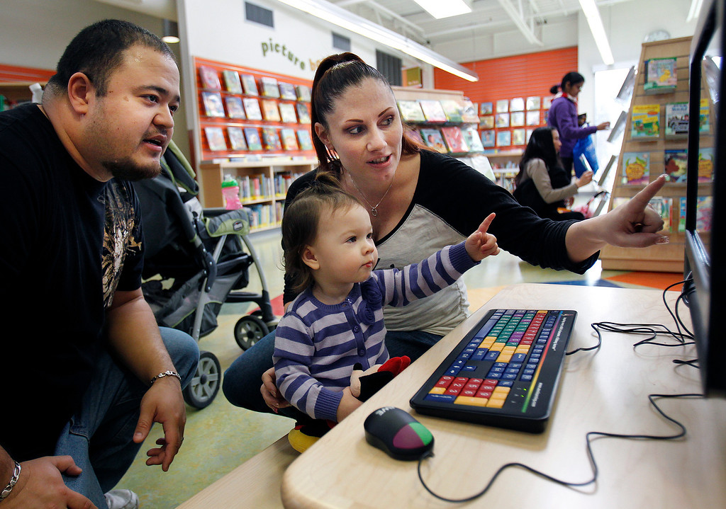 . From left, Alexander Nguyen, his 17-month old daughter Lana Nguyen and his wife Windy Nguyen use the Sesame Street learning program at the Seven Trees Branch Library after its grand opening celebration, in San Jose, Calif. on Saturday, January 26, 2013.   (LiPo Ching/Staff)