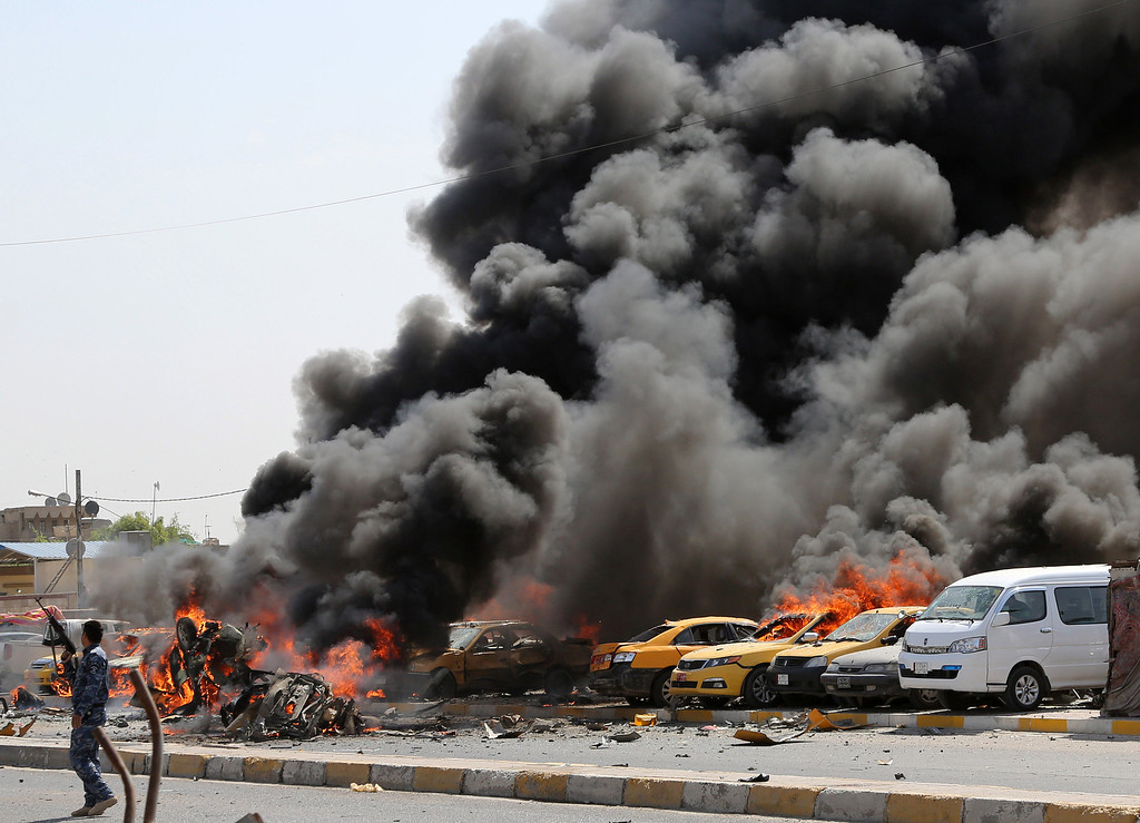 . An Iraqi policeman stands near burning vehicles moments after one in a series of bombs hit the Shiite stronghold of Sadr City, in Baghdad, Iraq, Tuesday, May 13, 2014.  (AP Photo/Karim Kadim)