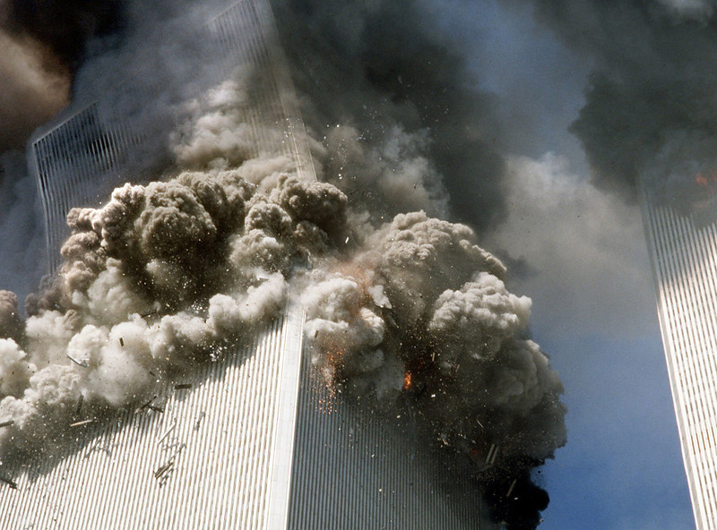 """. The south tower of New York\'s World Trade Center, left, begins to collapse after a terrorist attack on the buildings on Sept. 11, 2001. Federal investigators believe the second World Trade Center tower fell much more quickly than the first because it faced a more concentrated, intense fire inside, officials said Tuesday. Oct. 19, 2004.  Investigators have singled out this Associated Press photograph that they said may provide evidence to support their theory which shows a \""""kink\"""" in the building\'s corner at the 106th floor.  (AP Photo/Gulnara Samoilova, FILE)"""