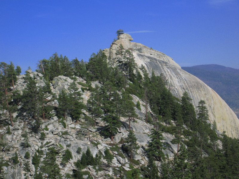 the lookout tower is perched on top ot a large rock dome