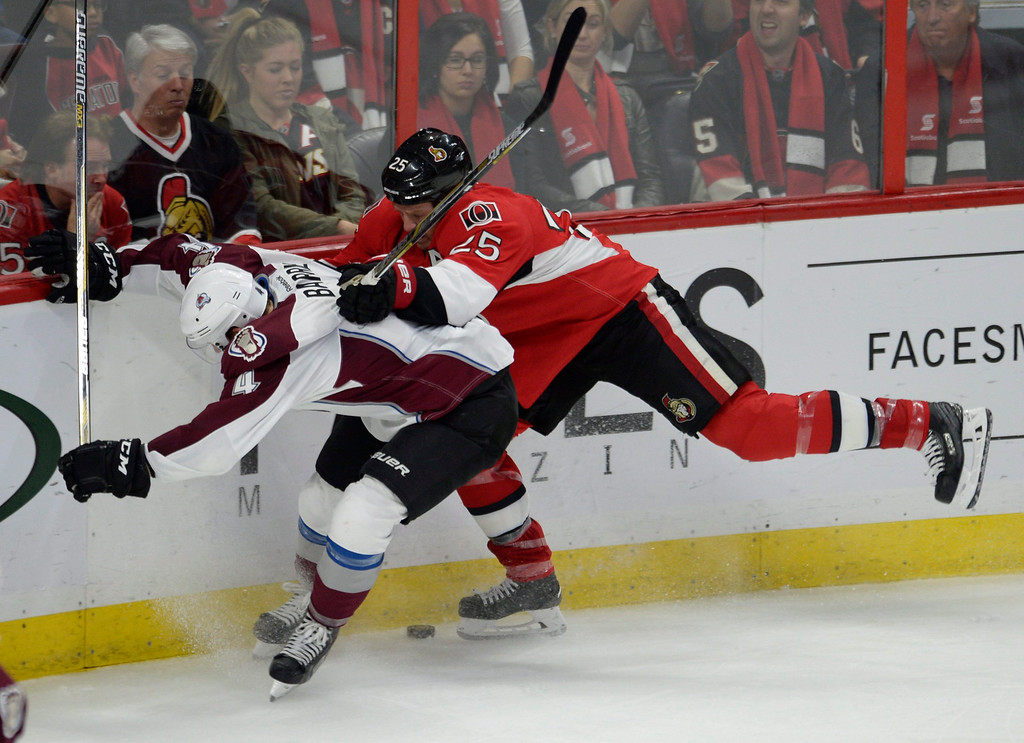 . Ottawa Senators\' Chris Neil (25) checks Colorado Avalanche\'s Tyson Barrie (4) during the third period of an NHL hockey game Thursday, Oct. 16, 2014, in Ottawa, Ontario. The Senators won 5-3. (AP Photo/The Canadian Press, Justin Tang)