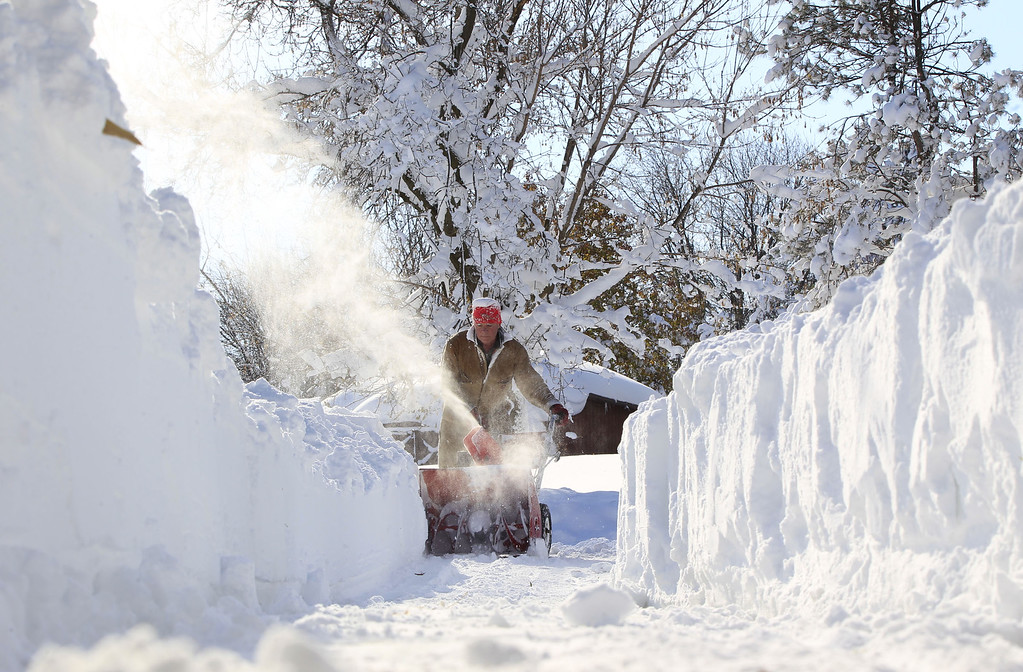 . Paul Lorenzo clears snow along Powers Road in Orchard Park, N.Y. on  Wednesday, Nov. 19, 2014.  A ferocious lake-effect storm left the Buffalo area buried under 6 feet of snow Wednesday, trapping people on highways and in homes, and another storm expected to drop 2 to 3 feet more was on its way. (AP Photo/The Buffalo News, Harry Scull Jr.)