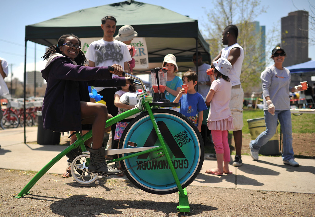 . DENVER, CO. - MAY 11 : Gabrielle Hollowell, 11, makes a smoothie with Bike-powered fruit smoothie blender from Groundwork Denver at Five Points in Denver, Colorado. May 11, 2013. People are celebrating the Five Points Better Block Project at Sonny Lawson Park. The event was an opportunity for The Five Points Better Block Project to demonstrate potential improvements for the neighborhood and provide tips to promote a stronger community. (Photo By Hyoung Chang/The Denver Post)