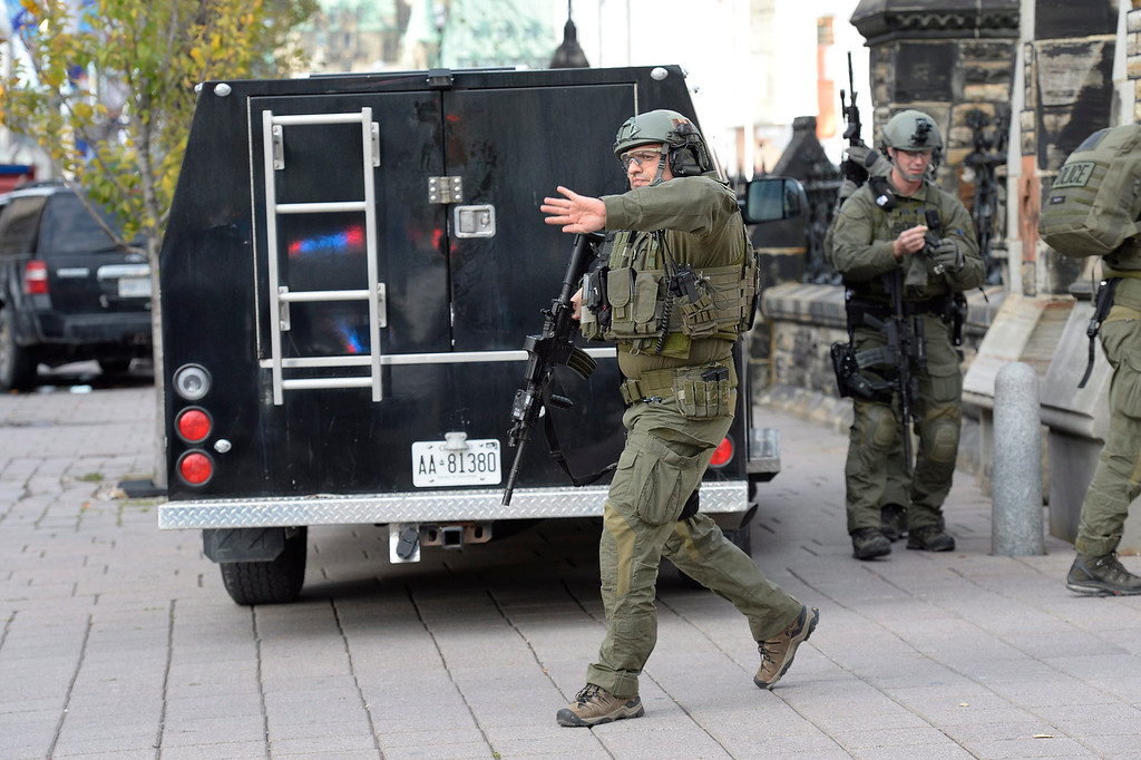 . RCMP intervention team members clear the area at the entrance of Parliament hill in Ottawa Wednesday Oct. 22, 2014.  A soldier standing guard at the National War Memorial was shot by an unknown gunman and people reported hearing gunfire inside the halls of Parliament. Prime Minister Stephen Harper was rushed away from Parliament Hill to an undisclosed location, according to officials. (AP Photo/The Canadian Press, Adrian Wyld)