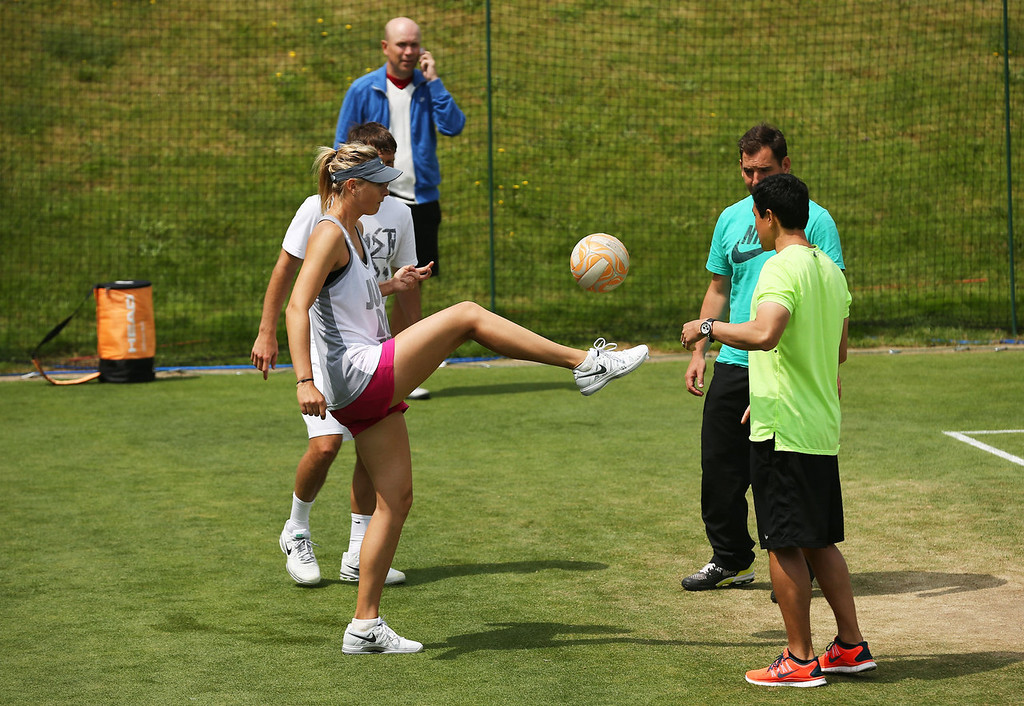 . Maria Sharapova of Russia kicks a football during a practice session with members of her coaching team on day two of the Wimbledon Lawn Tennis Championships at the All England Lawn Tennis and Croquet Club on June 25, 2013 in London, England.  (Photo by Dan Kitwood/Getty Images)