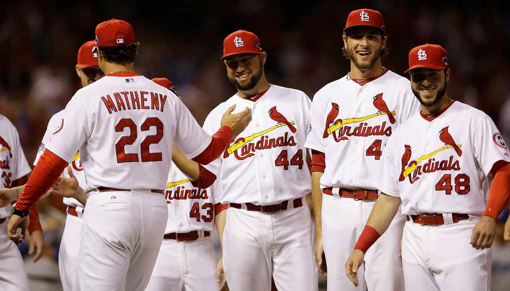 . St. Louis Cardinals manager Mike Matheny (22) greets players before the first inning of Game 1 of the National League baseball championship series against the Los Angeles Dodgers, Friday, Oct. 11, 2013, in St. Louis. (AP Photo/Jeff Roberson)