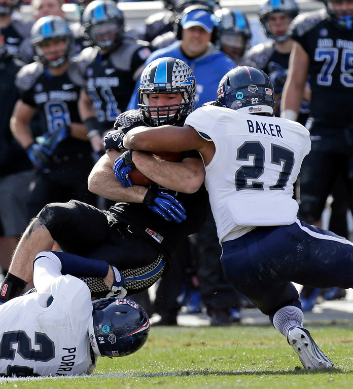 . Air Force running back Mike DeWitt is wrapped up by Rice safeties Paul Porras (24) and Gabe Baker (27) after a gain during the first half of the Armed Forces Bowl NCAA college football game, Saturday, Dec. 29, 2012, in Fort Worth, Texas. . (AP Photo/LM Otero)