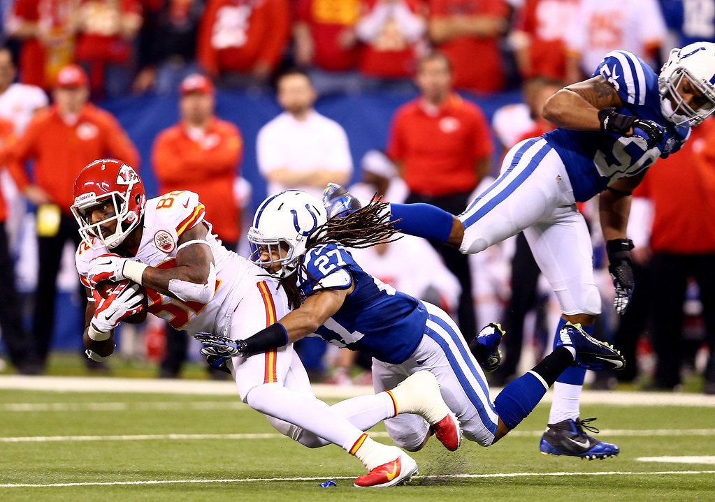 . INDIANAPOLIS, IN - JANUARY 04: Wide receiver Dwayne Bowe #82 of the Kansas City Chiefs is tackled by defensive back Josh Gordy #27 of the Indianapolis Colts during a Wild Card Playoff game at Lucas Oil Stadium on January 4, 2014 in Indianapolis, Indiana.  (Photo by Andy Lyons/Getty Images)