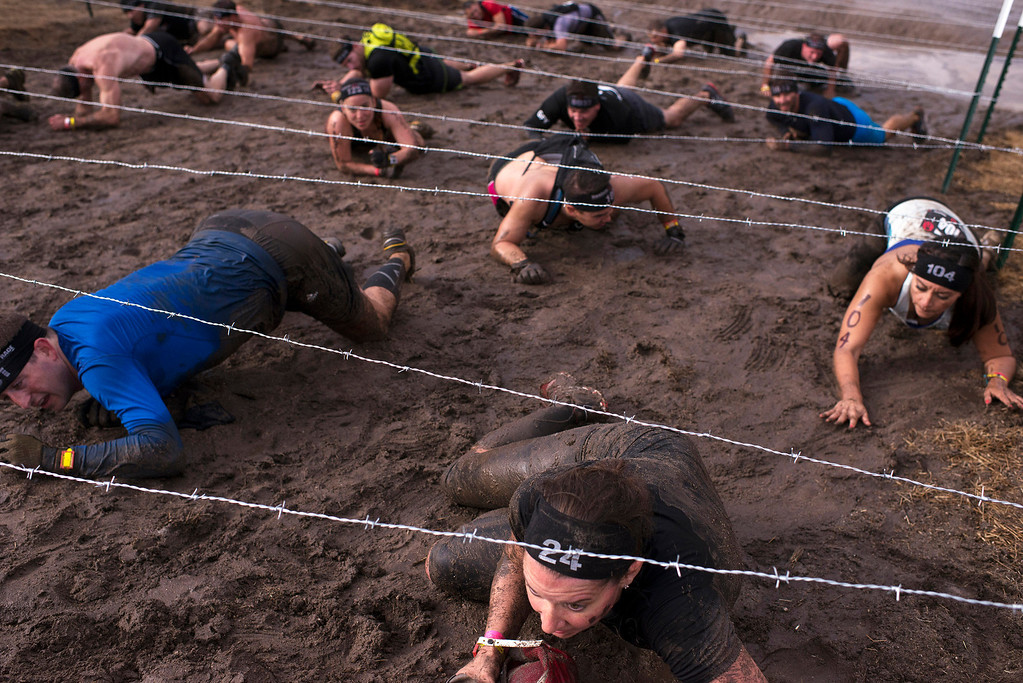. Spartan Race competitors crawl carefully beneath a barbed wire obstacle Saturday, August 10th, 2013. (Matthew Hintz/Monterey County Herald)