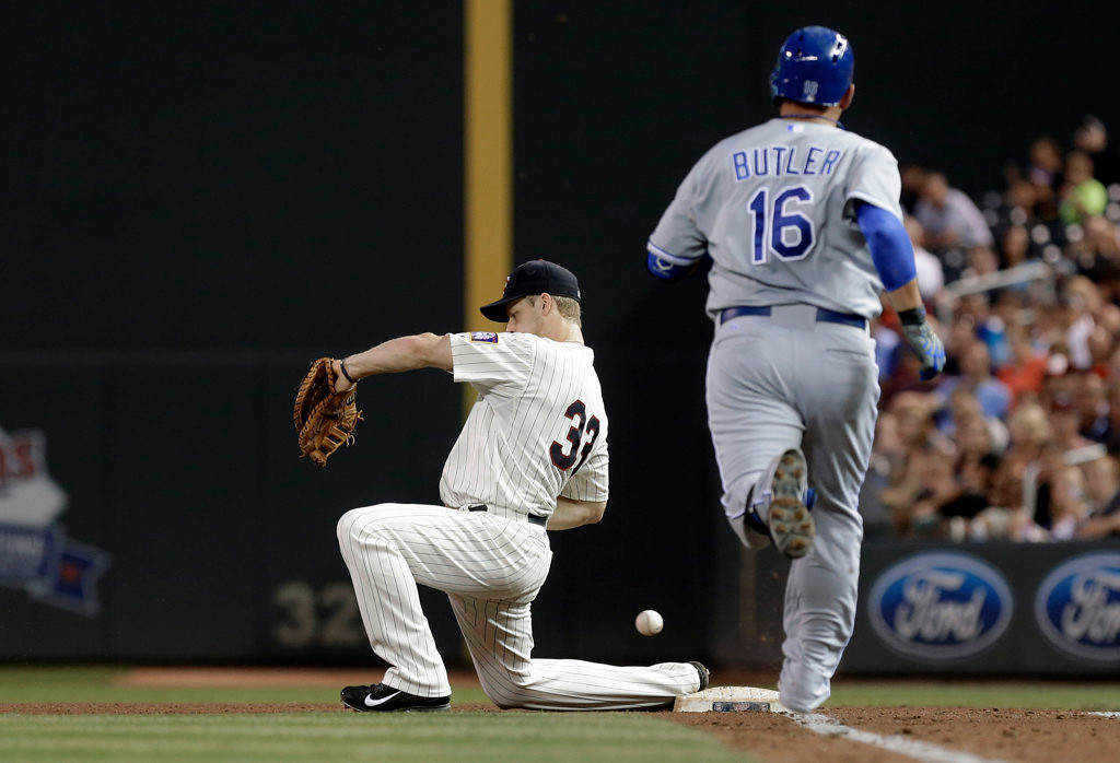 . Kansas City Royals\' Billy Butler (16) reaches first safely as Minnesota Twins first baseman Justin Morneau can\'t handle the errant throw by third baseman Trevor Plouffe in the fourth inning of a baseball game. (AP Photo/Jim Mone)