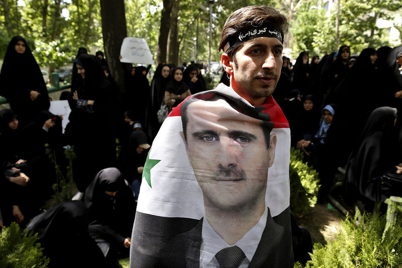 . A Syrian man wrapped in a Syrian flag with a portrait of President Bashar Assad, attends an anti-Israeli demonstration in front of the UN office in Tehran, Iran, Monday, May 6, 2013. Iran Condemns Israeli Air strikes on Syria and urged countries in the region to stand against the attack. (AP Photo/Ebrahim Noroozi)