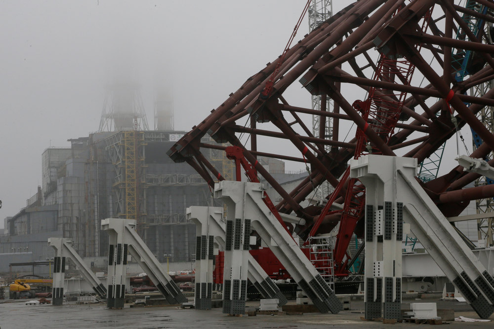 . Construction workers assist in the assembly of a gigantic steel-arch to cover the remnants of the exploded reactor at the Chernobyl nuclear power plant in Chernobyl, Ukraine, Tuesday, Nov. 27, 2012. The new safe confinement, a structure that is being built over reactor 4 damaged in 1986 as a result of the world\'s worst nuclear accident, will cover a hastily built sarcophagus, which was erected shortly after the explosion. (AP Photo/ Efrem Lukatsky)