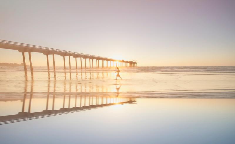 A lady walks a long Scripps Pier