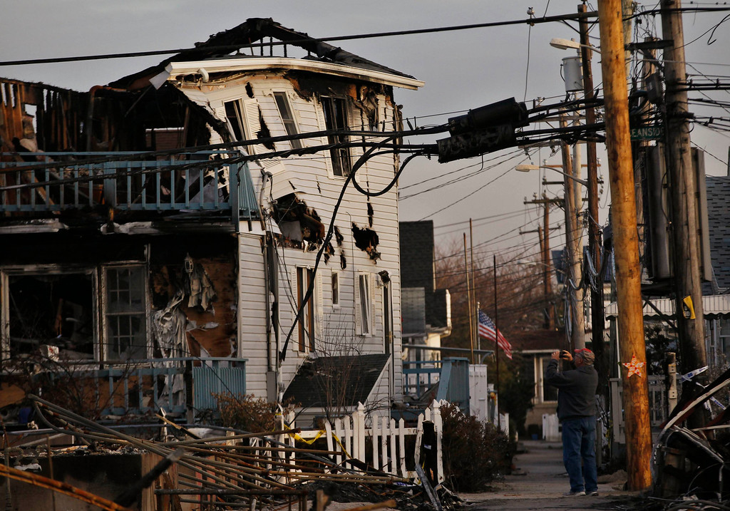 . A man photographs a storm damaged home, in the Breezy Point area of Queens, New York, November 28, 2012. REUTERS/Brendan McDermid