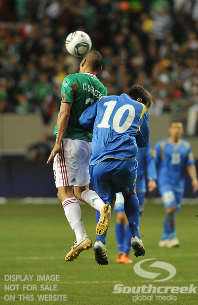Mexico's Defender Carlos Salcido (#3) heads the ball as Bosnia-Herzegovina's Midfielder Zvjezdan Misimovic (#10) attempts to get out of the way in Soccer action between Bosnia-Herzegovina and Mexico.  Mexico defeated Bosnia-Herzegovina 2-0 in the game at the Georgia Dome in Atlanta, GA.