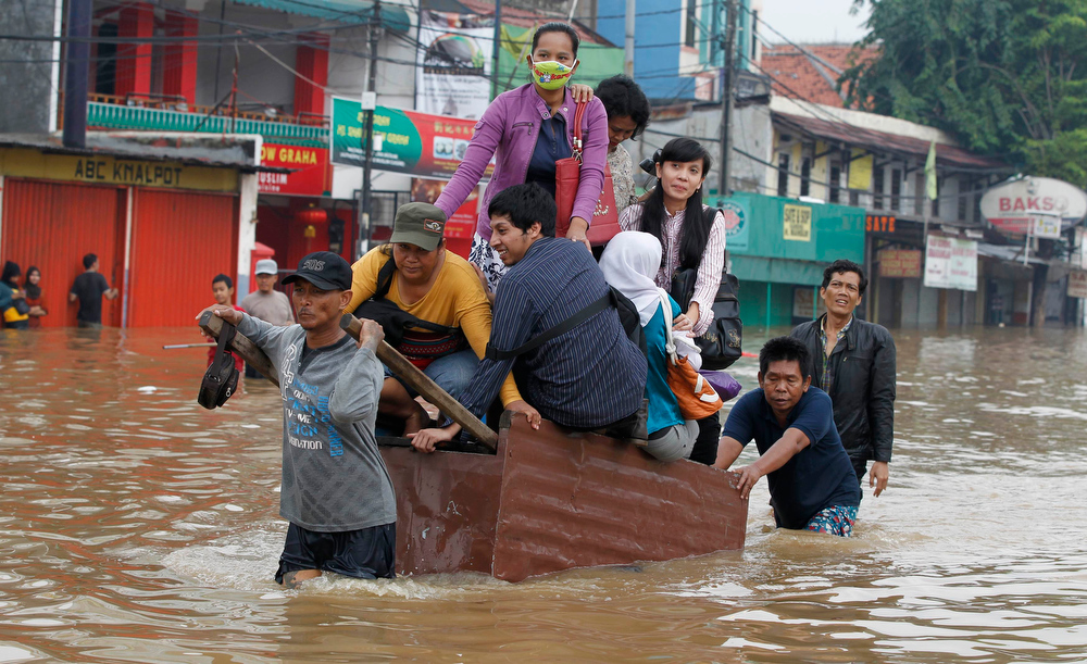 . People are transported across a flooded road on a wooden cart in Jakarta January 16, 2013. Thousands of residents are being evacuated after floods inundated several areas of Jakarta due to the overflow of the Ciliwung River and several days of heavy rains in the capital city, local media reported on Wednesday.   REUTERS/Enny Nuraheni