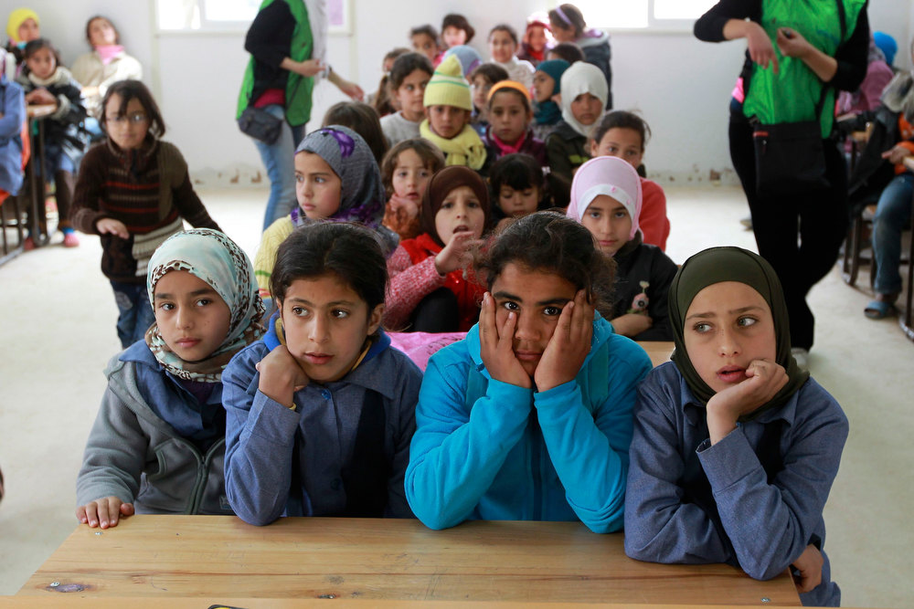 Description of . Syrian children, who are refugees, attend a class at Al- Zaatri refugee camp, in the Jordanian city of Mafraq, near the border with Syria February 12, 2013. The children resumed classes at school following a rainstorm three weeks ago that led the refugees at the camp to use the school building as a shelter. REUTERS/Muhammad Hamed