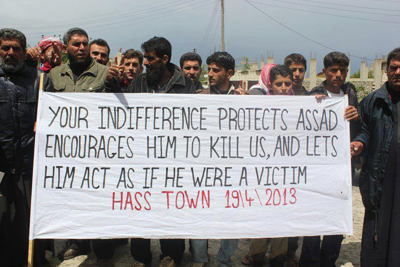 . This citizen journalism image provided by Edlib News Network, ENN, which has been authenticated based on its contents and other AP reporting, shows anti-Syrian regime protesters carrying a banner during a demonstration, at Hass Nabil town, in Idlib province, northern Syria, Friday April 19, 2013. Gunmen killed a government official in a Damascus restaurant, Syrian state media and activists reported Friday as regime troops and rebels fought fierce battles near the Lebanese border. (AP Photo/Edlib News Network ENN)