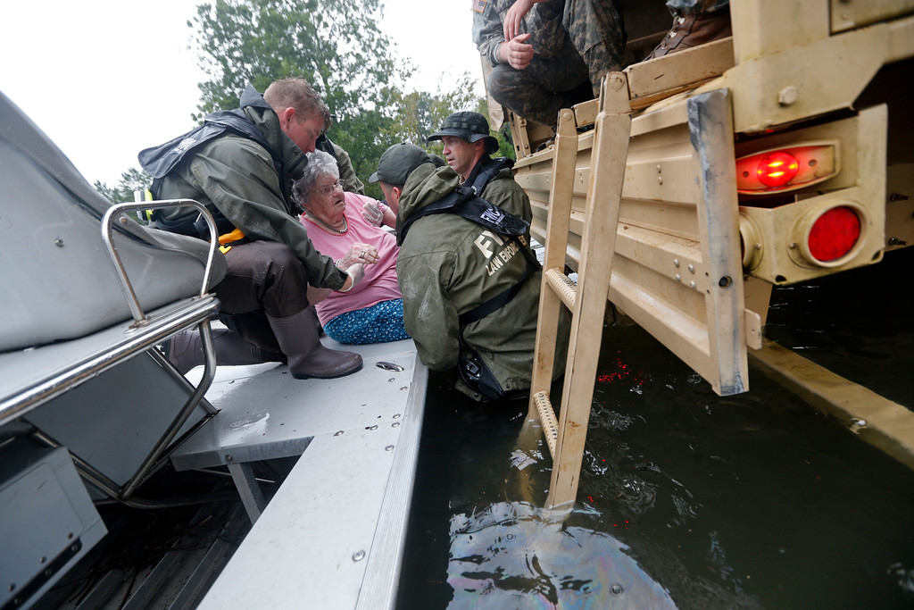 . Members of the Louisiana Department of Wildlife and Fisheries, the Florida Fish and Wildlife Conservation Commission, and the Louisiana National Guard help rescue with elderly people from the Golden Years Assisted Living home, which was flooded from Tropical Storm Harvey in Orange, Texas, Wednesday, Aug. 30, 2017. The residents and staff were high and dry on the second floor. (AP Photo/Gerald Herbert)