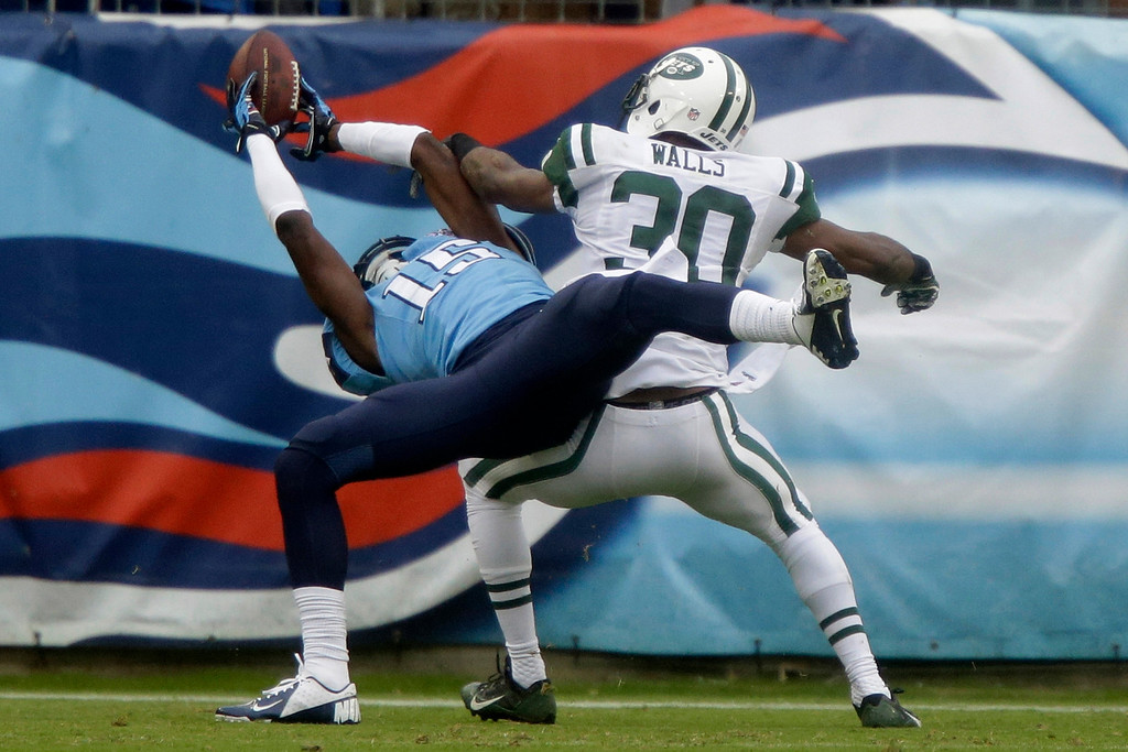 . Tennessee Titans wide receiver Justin Hunter (15) catches a 16-yard touchdown pass as he is defended by New York Jets cornerback Darrin Walls (30) in the second quarter of an NFL football game on Sunday, Sept. 29, 2013, in Nashville, Tenn. (AP Photo/Wade Payne)