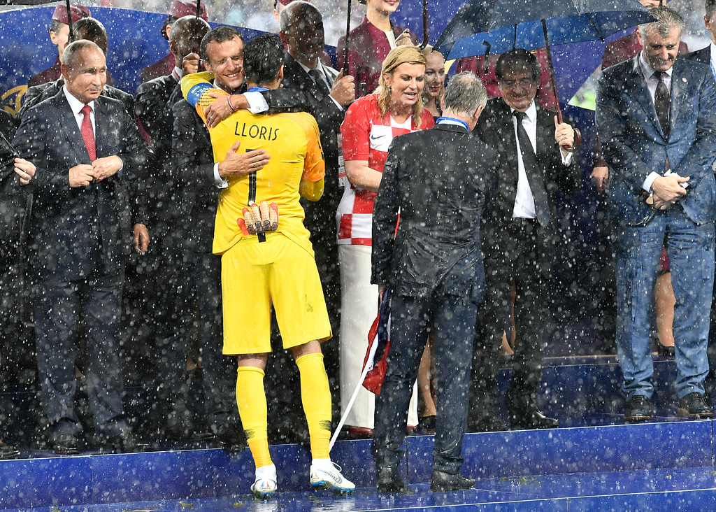 . Russian President Vladimir Putin, from left, looks on as French President Emmanuel Macron hugs France goalkeeper Hugo Lloris and Croatian President Kolinda Grabar-Kitarovic congratulates France head coach Didier Deschamps after France won 4-2 in the final match between France and Croatia at the 2018 soccer World Cup in the Luzhniki Stadium in Moscow, Russia, Saturday, July 14, 2018. (AP Photo/Martin Meissner)
