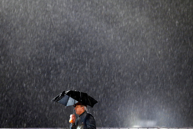 . A fan watches the race in the rain during the women\'s two-man bobsled competition at the 2014 Winter Olympics, Tuesday, Feb. 18, 2014, in Krasnaya Polyana, Russia. (AP Photo/Natacha Pisarenko)