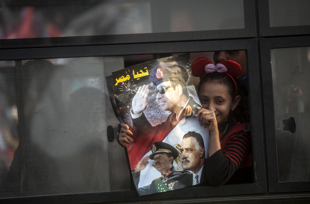 . An Egyptian girl looks out from a public bus as she holds a poster with a portrait of late president Gamal Abdel Nasser, Anwar Sadat and Egypt\'s Defense Minister General Abdel Fattah al-Sisi outside a polling station during the vote on a new constitution on January 14, 2014 in Giza, Cairo. Egyptians queued to vote on a new constitution today amid high security, in a referendum likely to launch a presidential bid by the army chief who overthrew Islamist president Mohamed Morsi.  (MAHMOUD KHALED/AFP/Getty Images)