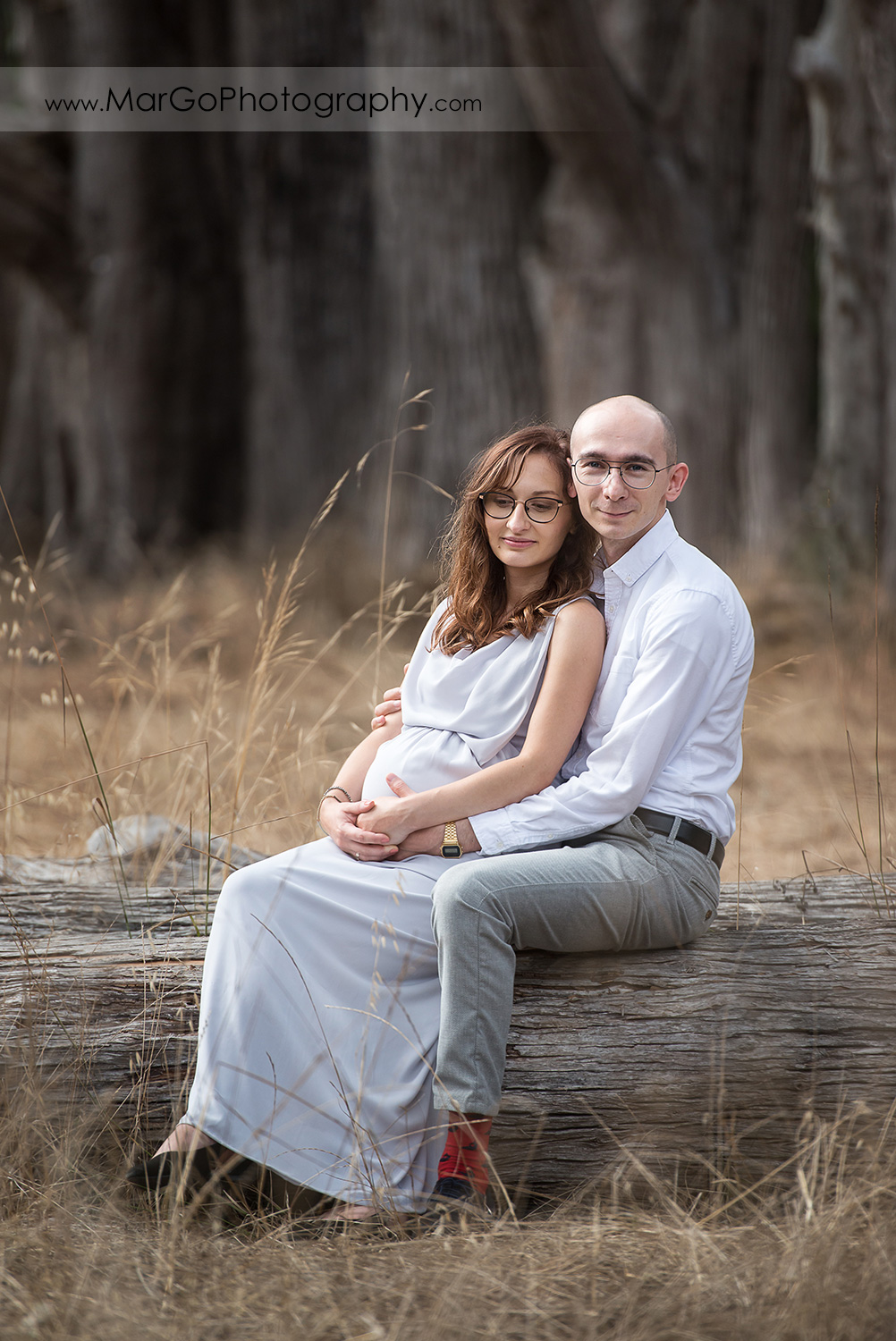 man and pregnant woman in long gray sitting on the cypress tree