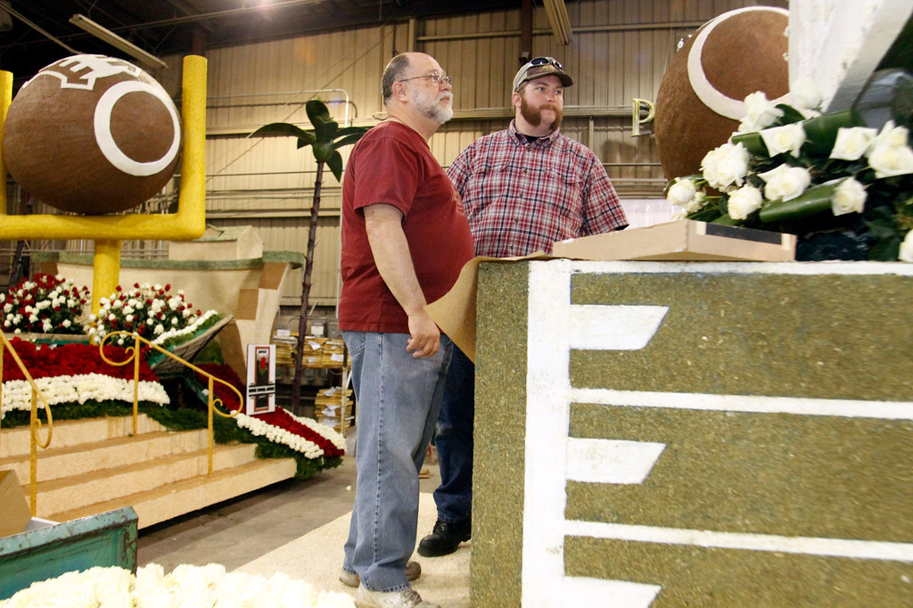 ". Jon Olson, with his son Andrew Olson, of Claremont, right, check out  the details that still need to be finished on the Michigan State\'s 2013 Tournament of Roses Parade Float, at the Artistic Entertainment Services in Azusa, CA., Tuesday, December 31, 2013. Jon Olson a ""float operator\"" has been driving Rose Parade floats for years, this year he has been chosen to drive the Michigan State float. (Photo by James Carbone for the Daily Bulletin)"