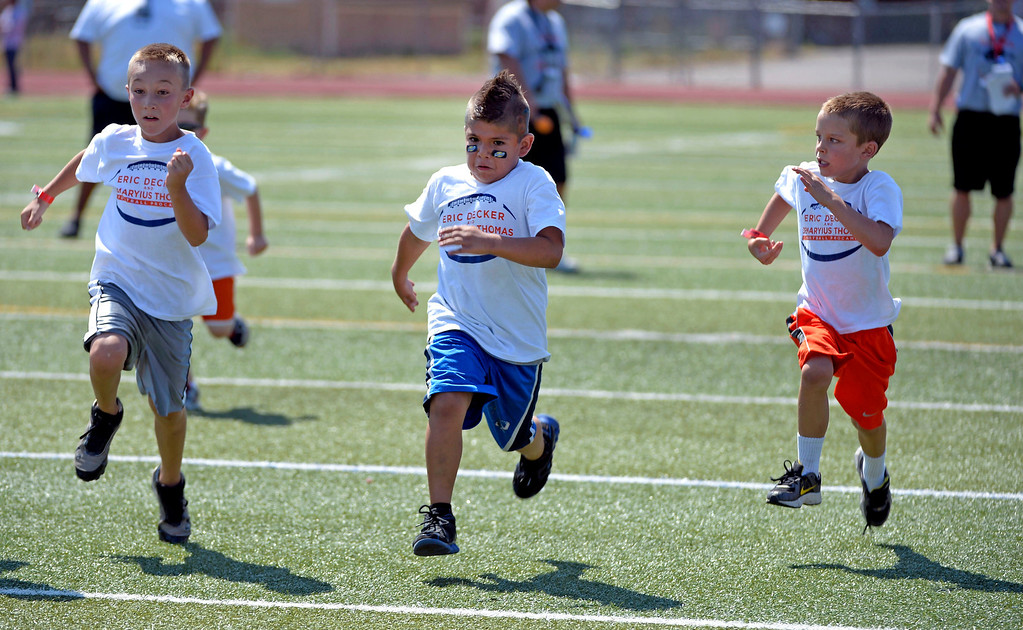 . Chase Cecil 8, Paolo Tafoya 7, and Griffin Courtney 8 sprint to the finish line during a race at camp. Demaryius Thomas and Eric Decker team up with ProCamps for their football camp held at Littleton High School July 11, 2013.  (Photo By John Leyba/The Denver Post)