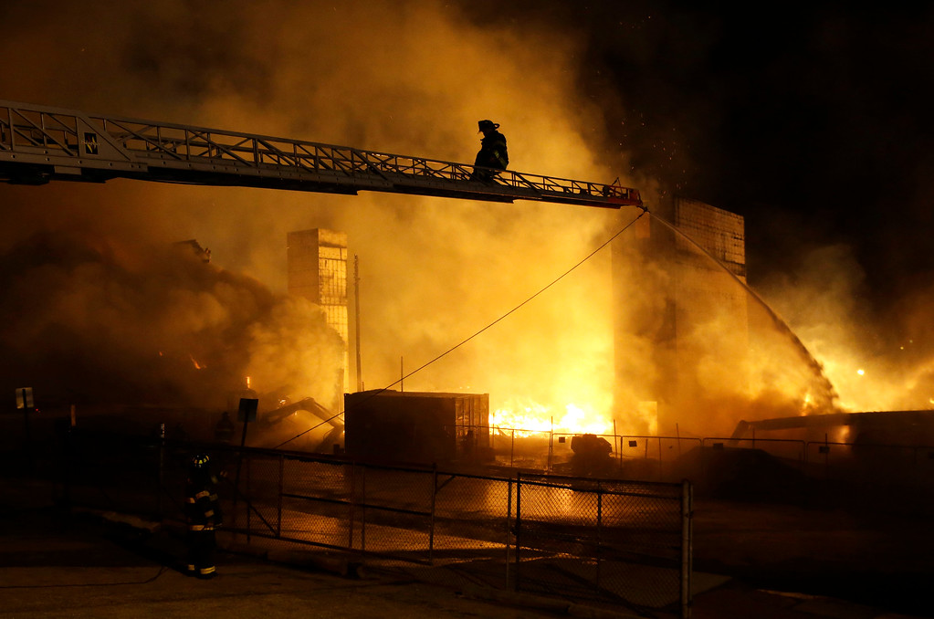 . Firefighters battle a blaze, Monday, April 27, 2015, after rioters plunged part of Baltimore into chaos, torching a pharmacy, setting police cars ablaze and throwing bricks at officers.  (AP Photo/Patrick Semansky)