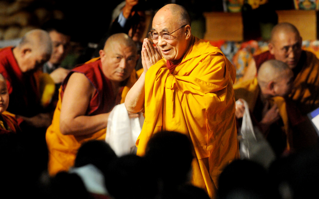 . The Dalai Lama gives the sign of prayer and respect to the 2,500 attending Losar at Augsburg College in Minneapolis as he exits the event Sunday, March 2, 2014, in Minneapolis.  (Pioneer Press: Sherri LaRose-Chiglo)