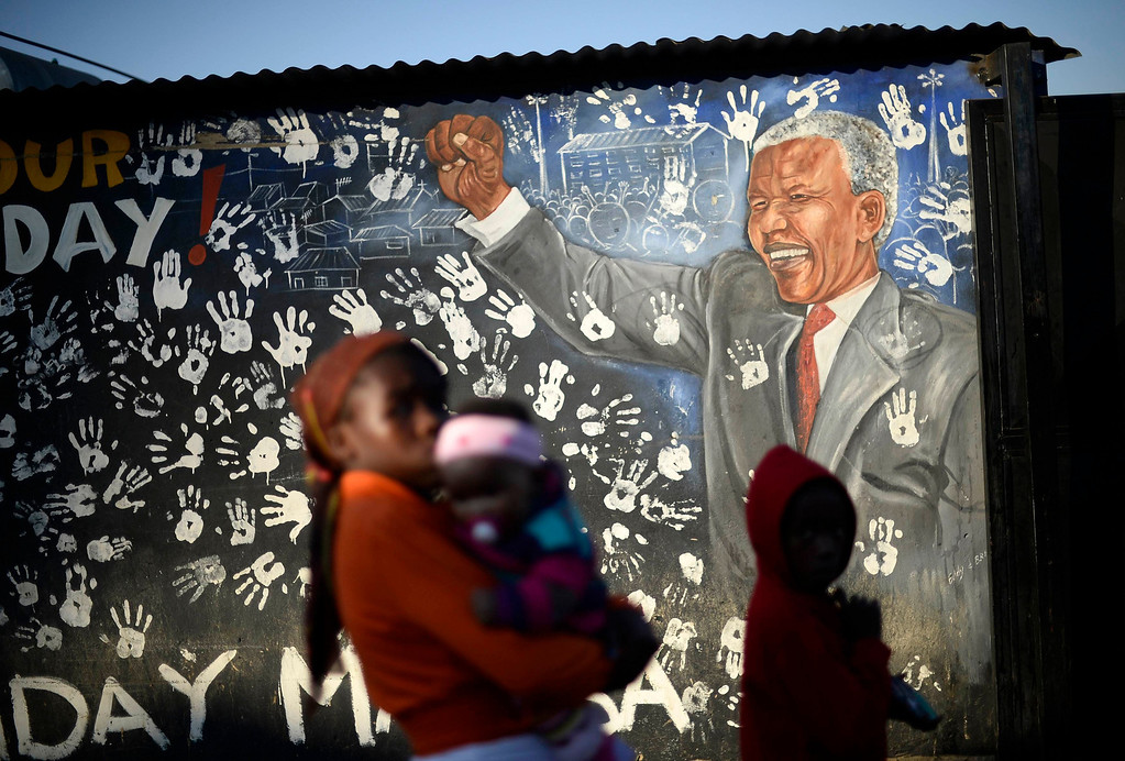 . Locals stroll past a mural, outside the house former President Nelson Mandela stayed in the 1940s, in Johannesburg\'s Alexandra township June 25, 2013. Mandela remains in a critical condition in hospital after being admitted more than two weeks ago with a lung infection, the government said on Tuesday. REUTERS/Dylan Martinez