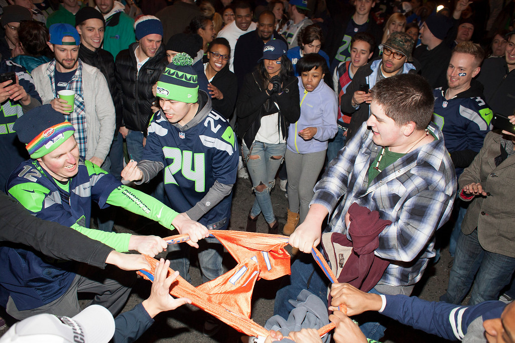 . Seattle Seahawks fans tear apart a Denver Broncos jersey in the middle of 1st Avenue on February 2, 2014 in Seattle, Washington. Hundreds of people flooded the streets of downtown Seattle after the Seahawks defeated the Denver Broncos in the Super Bowl.  (Photo by David Ryder/Getty Images)