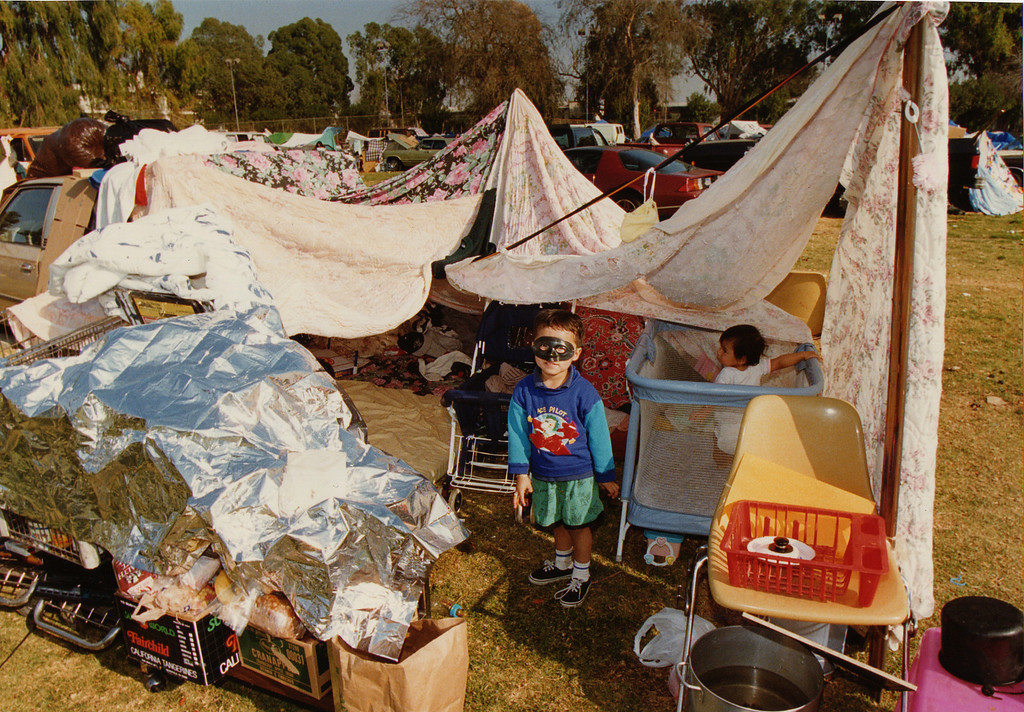 . A child stands in his grandmother\'s makeshift campsite at Lanark Park. Nearly 18,000 people camped out at local parks in the days following the quake. Concerned about health problems, officials worked to divert campers to Red Cross shelters and specially designated parks where services were concentrated. CA. 1/17/1994, photo by (John McCoy/Los Angeles Daily News)