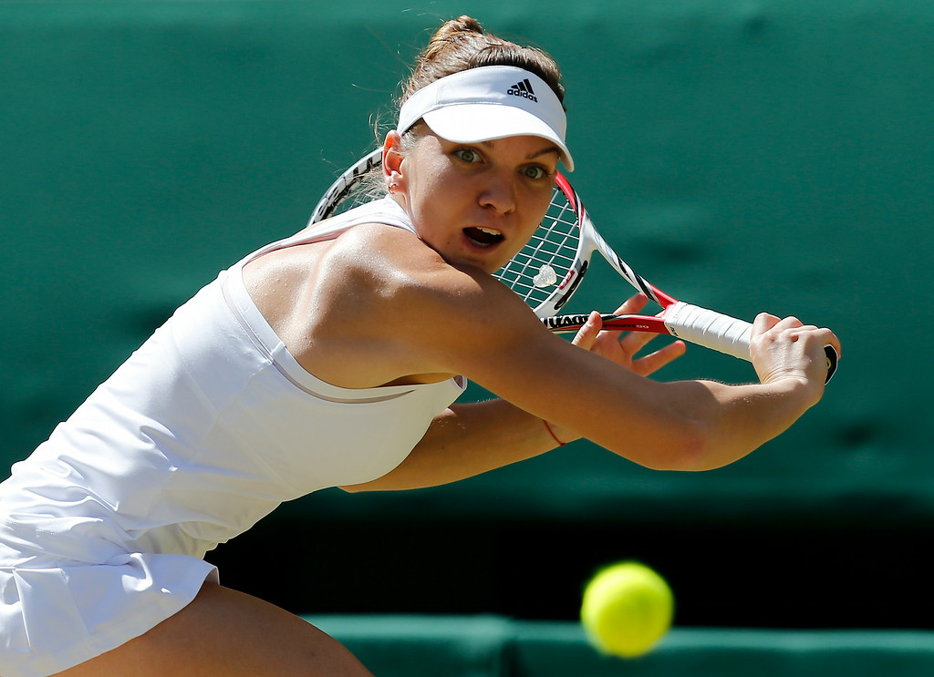 . Simona Halep of Romania plays a return to Eugenie Bouchard of Canada during their womenís singles semifinal match at the All England Lawn Tennis Championships in Wimbledon, London, Thursday, July 3, 2014. (AP Photo/Ben Curtis)