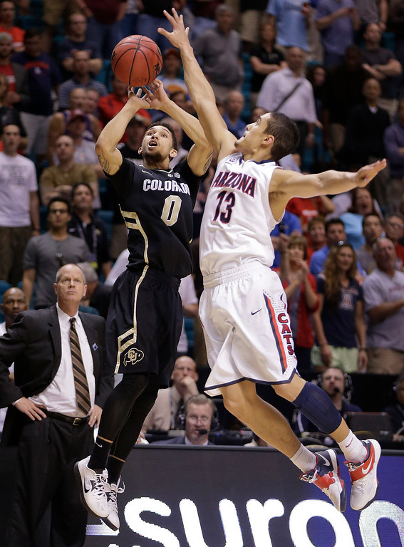 . Colorado\'s Askia Booker (0) shoots against Arizona\'s Nick Johnson late in the second half during a Pac-12 tournament NCAA college basketball game, Thursday, March 14, 2013, in Las Vegas. Johnson blocked the shot. Arizona won 79-69. (AP Photo/Julie Jacobson)