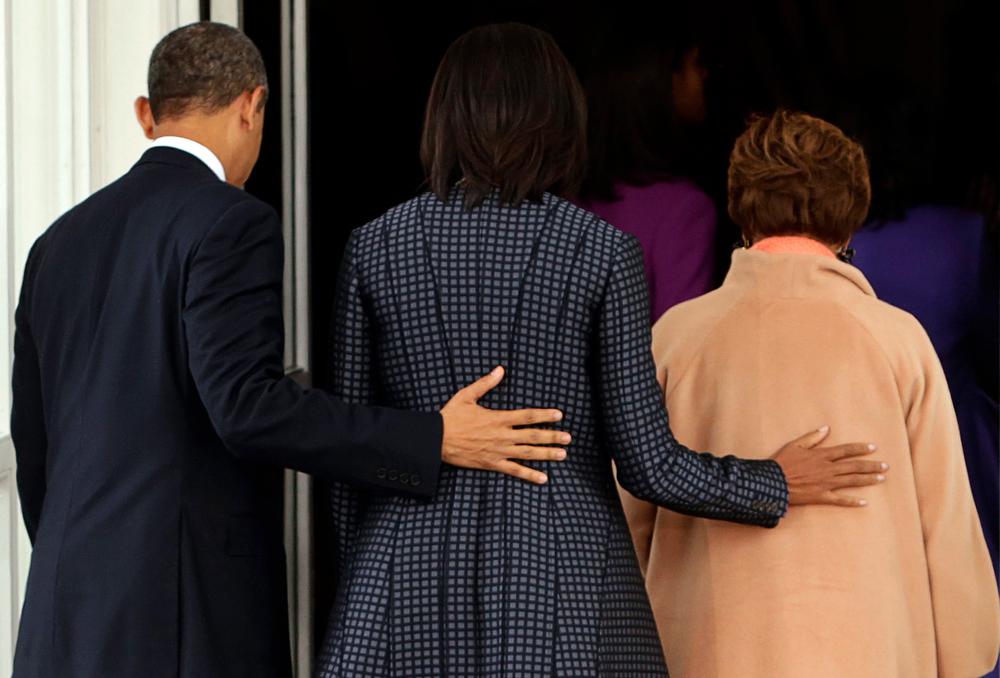 Description of . U.S. President Barack Obama (L) arrives back at the White House with First Lady Michelle Obama (C) and Michelle Obama's mother Marian Robinson (R) in Washington January 21, 2013, after attending service at St. John's Episcopal Church on the day of his ceremonial swearing-in for his second term. REUTERS/Chris Kleponis