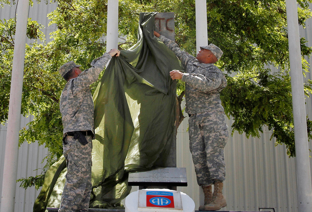 . In this Monday, May 31, 2010 file photo, U.S. soldiers unveil a steel construction beam from the World Trade Center destroyed in the Sept. 11, 2001 terrorist attacks during a ceremony marking the Memorial Day at the main U.S. base in Bagram north of Kabul, Afghanistan. More than 2,600 artifacts have gone to 1,585 fire and police departments, schools and museums, and other nonprofit organizations in every state and at least eight other countries. (AP Photo/Musadeq Sadeq)