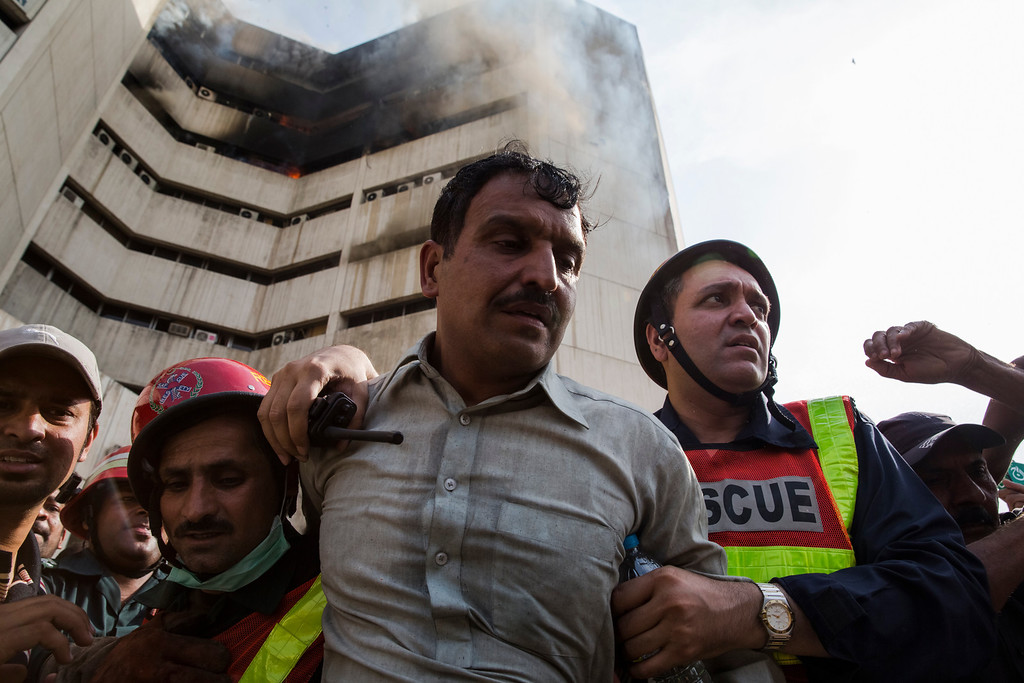 . A man suffering from smoke inhalation is rushed away after being rescued from a building as a fire still burns at the Lahore Development Authority (LDA) Plaza on May 09, 2013 in Lahore, Pakistan. (Photo by Daniel Berehulak/Getty Images)