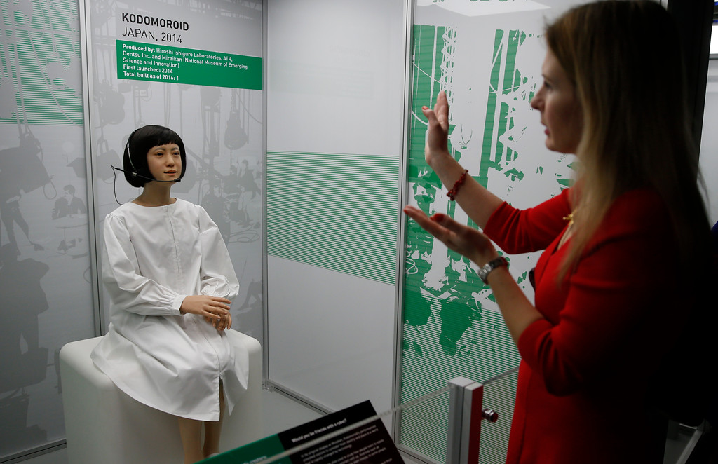 . A member of the media tries to attract the attention of Kodomoroid a life like Japanese robot, which is a designed robotic news reader for the Miraikan the Japanese national Museum of Emerging Science and Innovation, during a press preview for the Robots exhibition held at the Science Museum in London, Tuesday, Feb. 7, 2017. The exhibition which shows 500 years of mechanical and robotic advances is open to the public form Feb. 8 through to Sept. 3. (AP Photo/Alastair Grant)