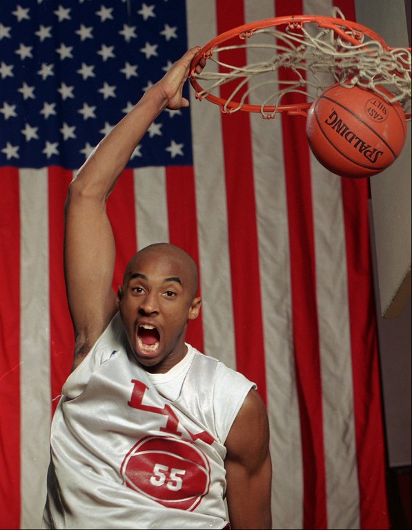 . FILE--With a large flag as a backdrop, Kobe Bryant dunks the ball at his Lower Merion, Pa. high school gym during a practice Friday, Jan. 19, 1996. Bryant was chosen by the Charlotte Hornets in the first round of the NBA draft Wednesday June 26, 1996 (AP Photo/rusty kennedy)