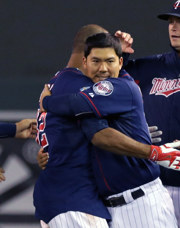 . Minnesota Twins\' Kurt Suzuki, right, hugs Aaron Hicks after Hicks\' walk-off single in the ninth inning of a baseball game against the Detroit Tigers, Tuesday, Sept. 16, 2014, in Minneapolis. Suzuki\'s double in the ninth tied the score. The Twins won 4-3. (AP Photo/Jim Mone)