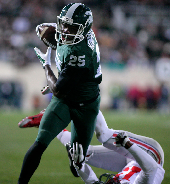 . Michigan State\'s Keith Mumphery (25) runs over Ohio State\'s Gareon Conley for a 15-yard touchdown on a pass reception during the first quarter of an NCAA college football game, Saturday, Nov. 8, 2014, in East Lansing, Mich. (AP Photo/Al Goldis)