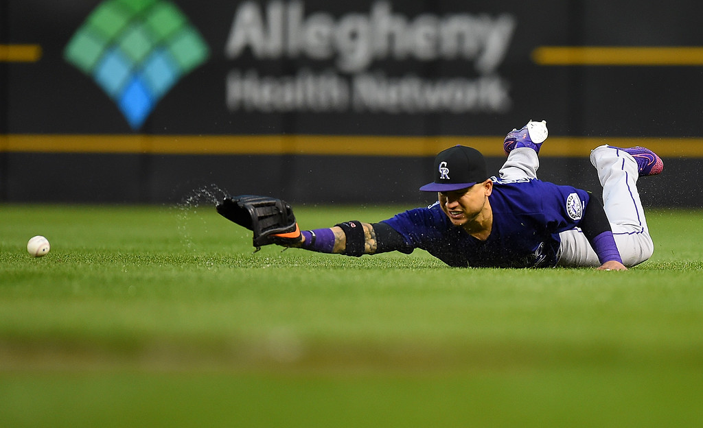 . PITTSBURGH, PA - MAY 21:  Carlos Gonzalez #5 of the Colorado Rockies can\'t make a catch on a ball hit by Josh Harrison #5 of the Pittsburgh Pirates (not pictured) during the ninth inning on May 21, 2016 at PNC Park in Pittsburgh, Pennsylvania.  (Photo by Joe Sargent/Getty Images)