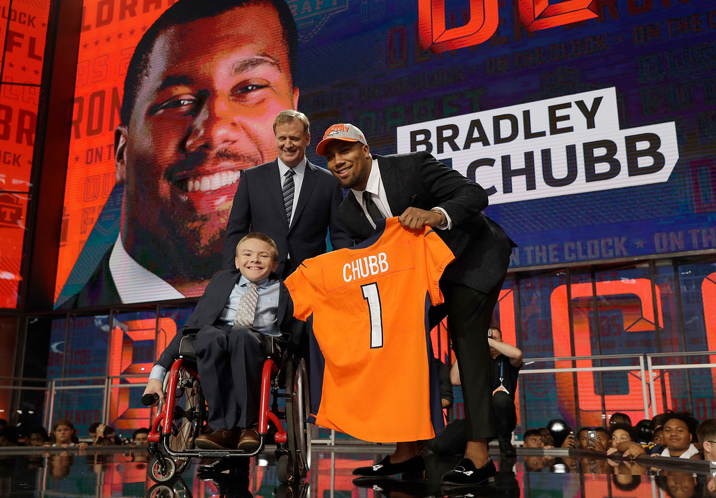 . North Carolina State\'s Bradley Chubb, right, poses with Commissioner Roger Goodell, top, and Austin Denton after being picked by the Denver Broncos during the first round of the NFL football draft, Thursday, April 26, 2018, in Arlington, Texas. (AP Photo/David J. Phillip)